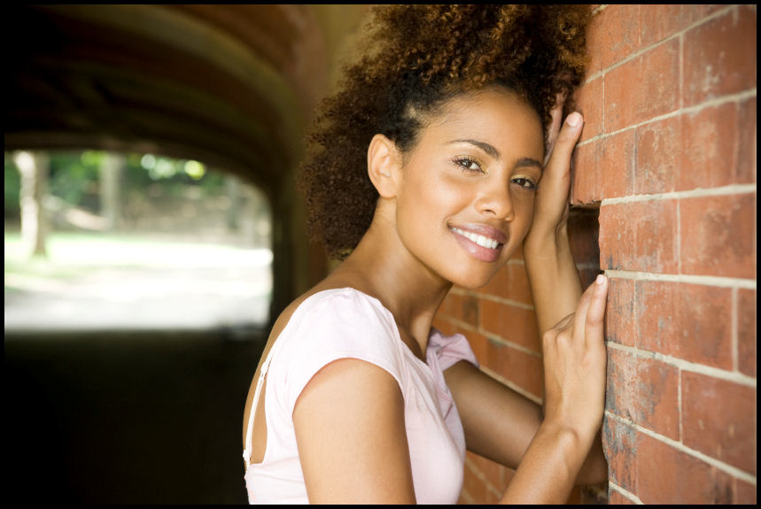 stylish-curly-hair-woman-against-brick-with-broder.jpg